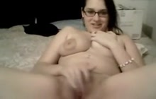 Busty babe in glasses rubbing her smooth pussy